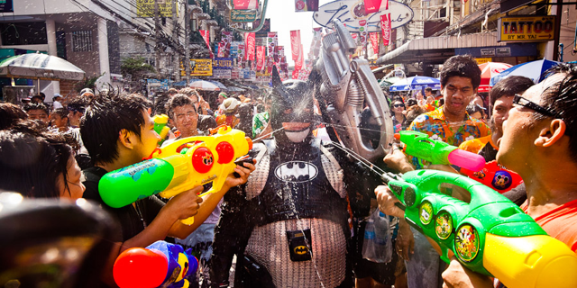 person in batman suit getting soaked by people with water guns