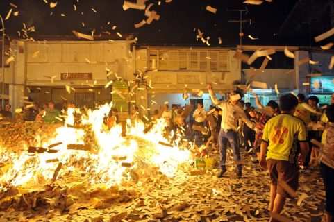 "crowd burning mounds of paper ""hell notes"""