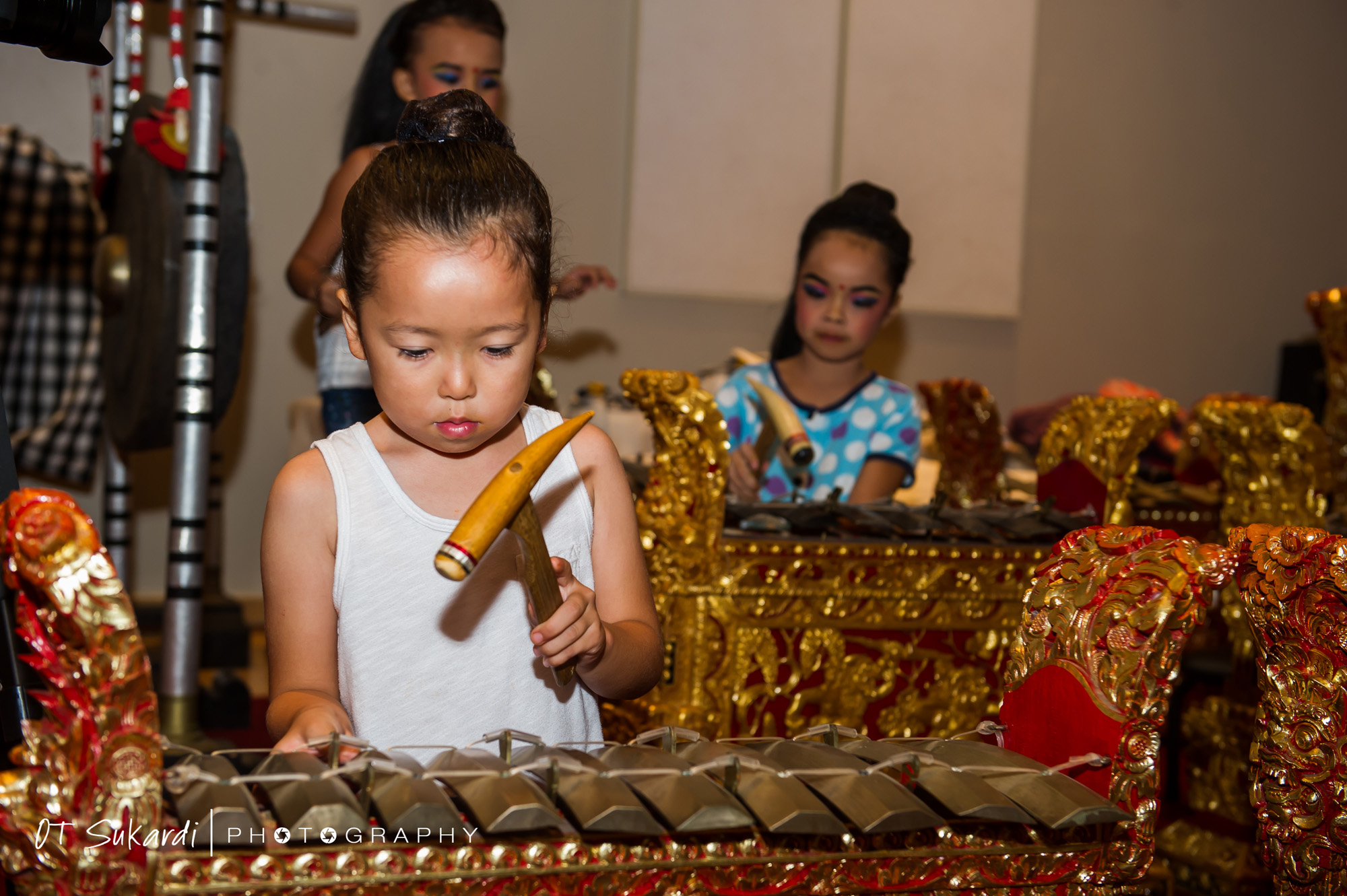 Young girl hammers on part of gamelan