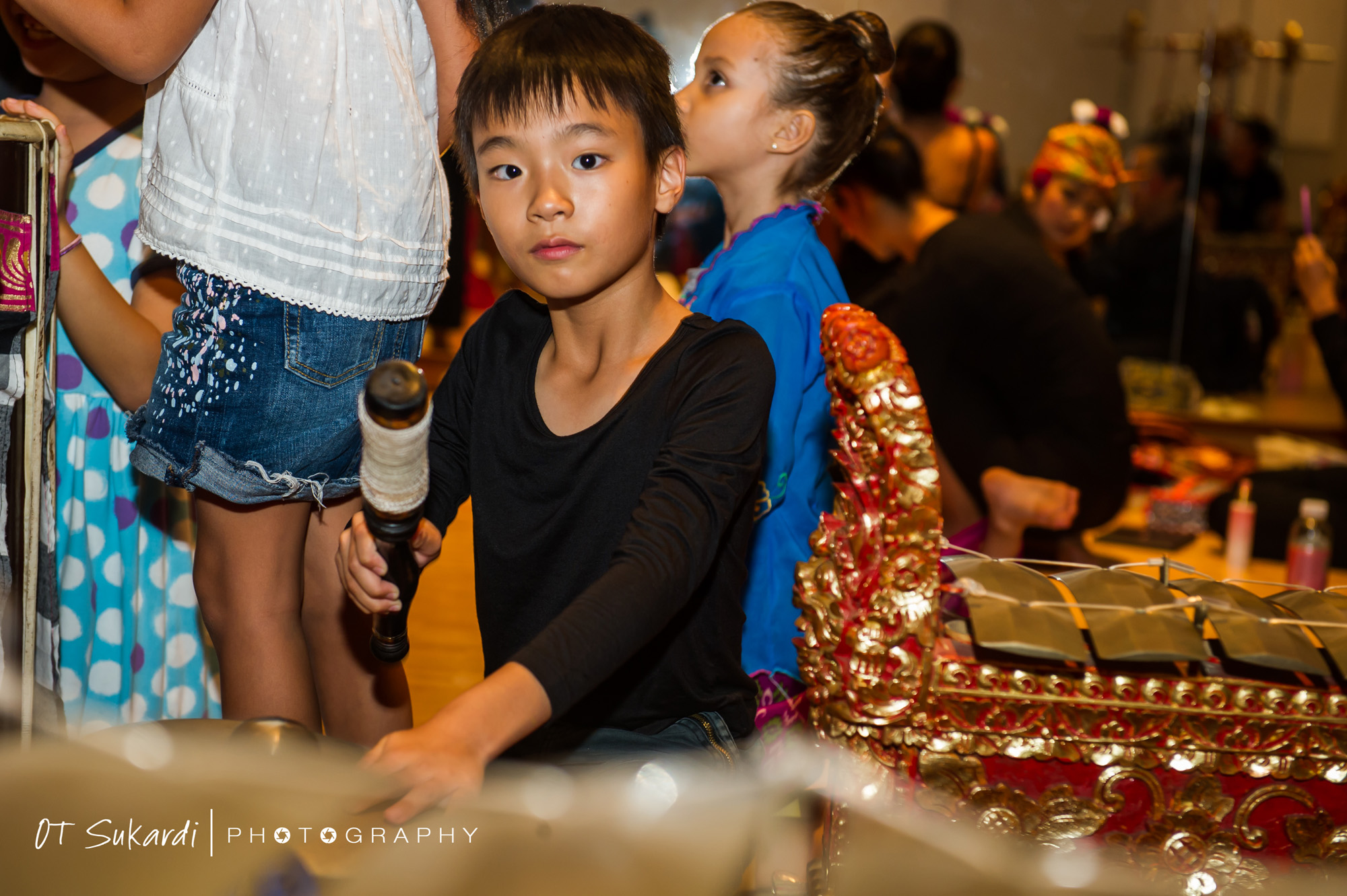 Boy hammers on part of gamelan