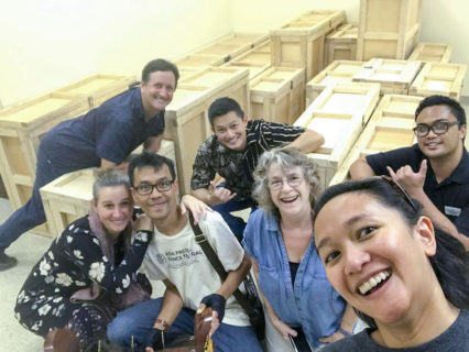 team gamelan - a group of smiling people pose in front of wooden crates